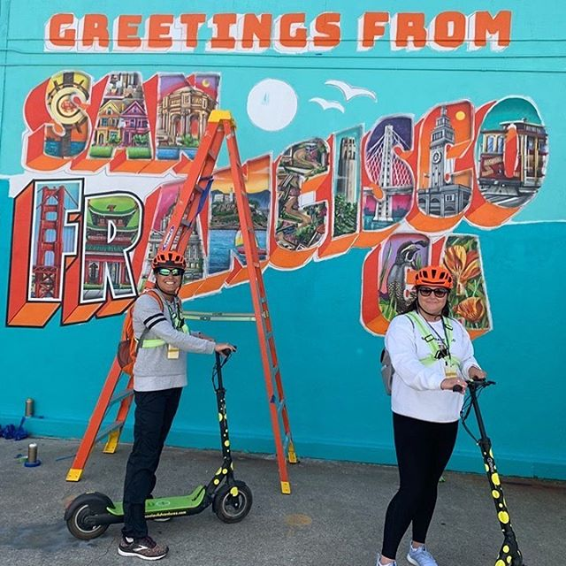 It's Wednesday- Greetings From San Francisco - todays guests checking out the new @greetingsfromsanfran mural . Artist @maxfieldbala is almost finished painting this epic wall in @fishermanswharf at our office. Take one of our e-scooter 🛴 tours to the world 🌎 famous Golden Gate Bridge!  Get out and enjoy the day in on one of our fully guided tours. In no time at all you will be taking in the beautiful views from the South end of the famous Gg Bridge span. Fully guided tours start from and travel to the on our kick-butt electric scooter 🛴tours. 2.5 hours of riding fun with our entertaining tour guides. Our fully guided E-scooter 🛴 tours are also available at our location too! . . . . Book online Https://SFscooteradventures.com or call 415-474-3130 . . . .